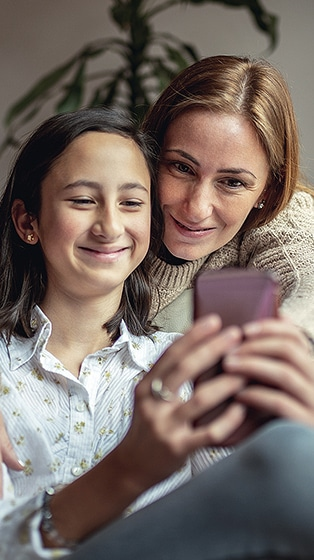 Mom and daughter looking at phone together