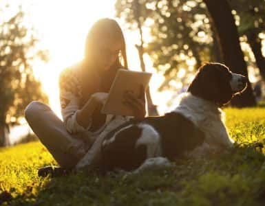 "alt=""woman enjoying the sun outdoors in sunset with dog using tablet""/>"